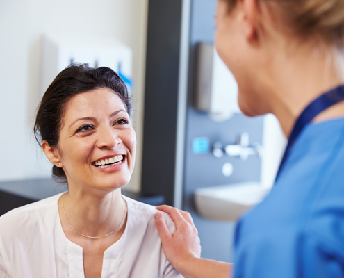 A healthcare provider in scrubs interacting with a patient